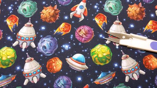 Detalle tela infantil con dibujos de cohetes y meteoritos